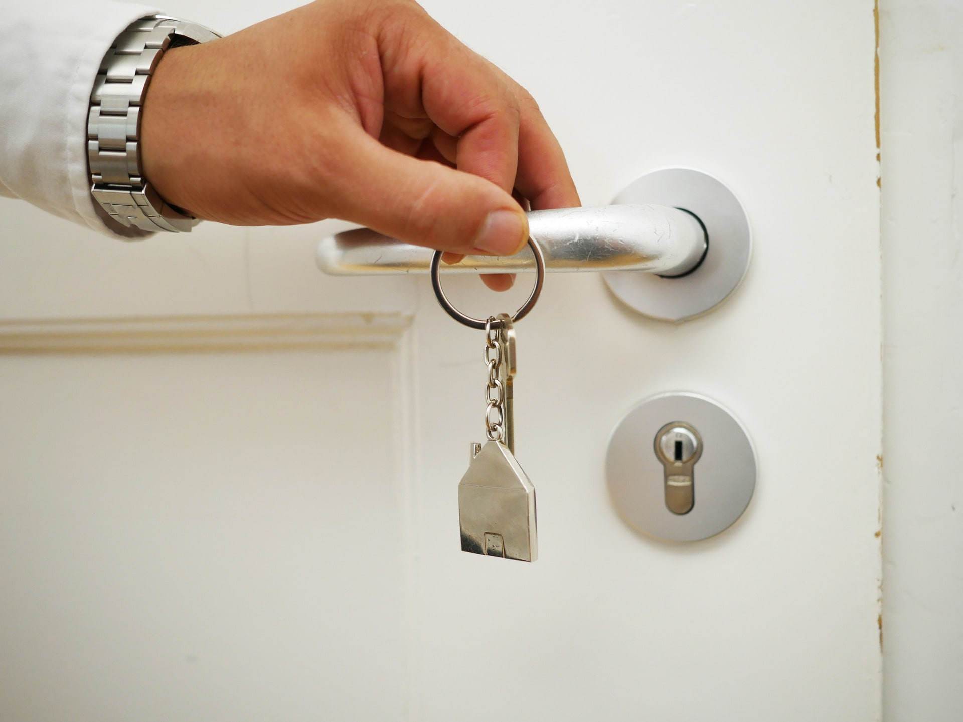 An image of the person holding the door with keychain